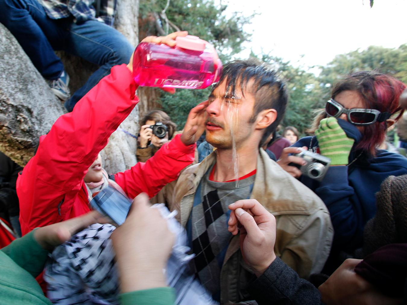 this Friday, Nov. 18, 2011, photo occupy protester David Buscho is helped after being pepper sprayed by campus police while blocking their exit from the school