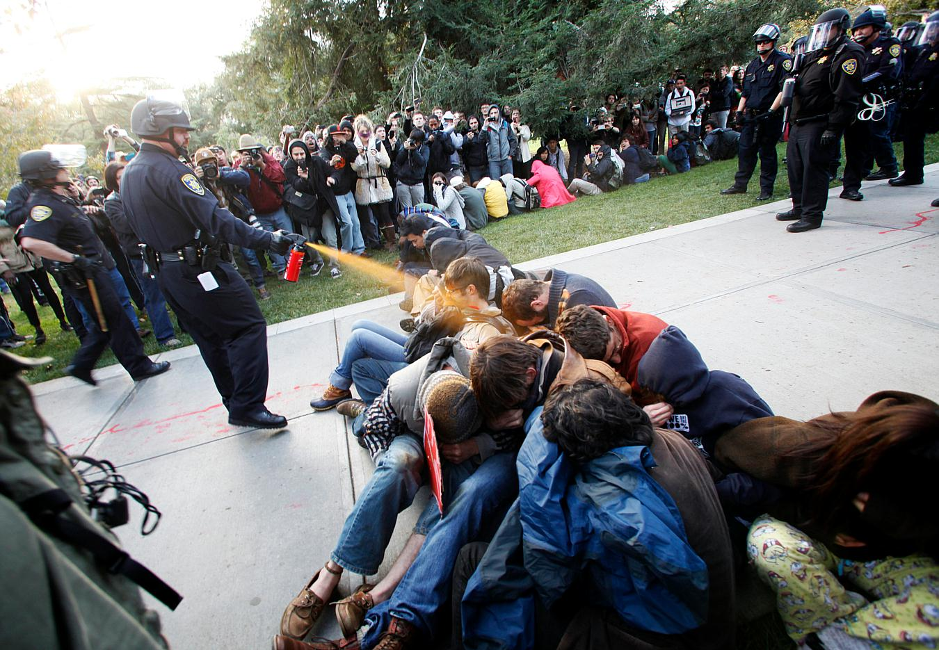 In this Friday, Nov. 18, 2011, photo University of California, Davis Police Lt. John Pike uses pepper spray to move Occupy UC Davis protesters while blocking their exit from the school