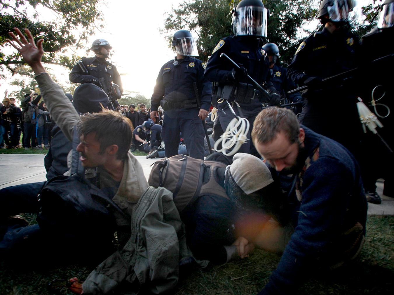 In this Friday, Nov. 18, 2011, photo Occupy University of California, Davis, protesters including David Buscho, far left, react after being pepper sprayed by police who came to remove tents set up on the school