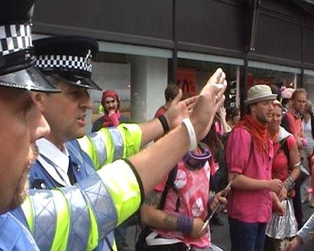 Police telling the pinks to back away. Note the Police Office is wearing an MPH wristband.